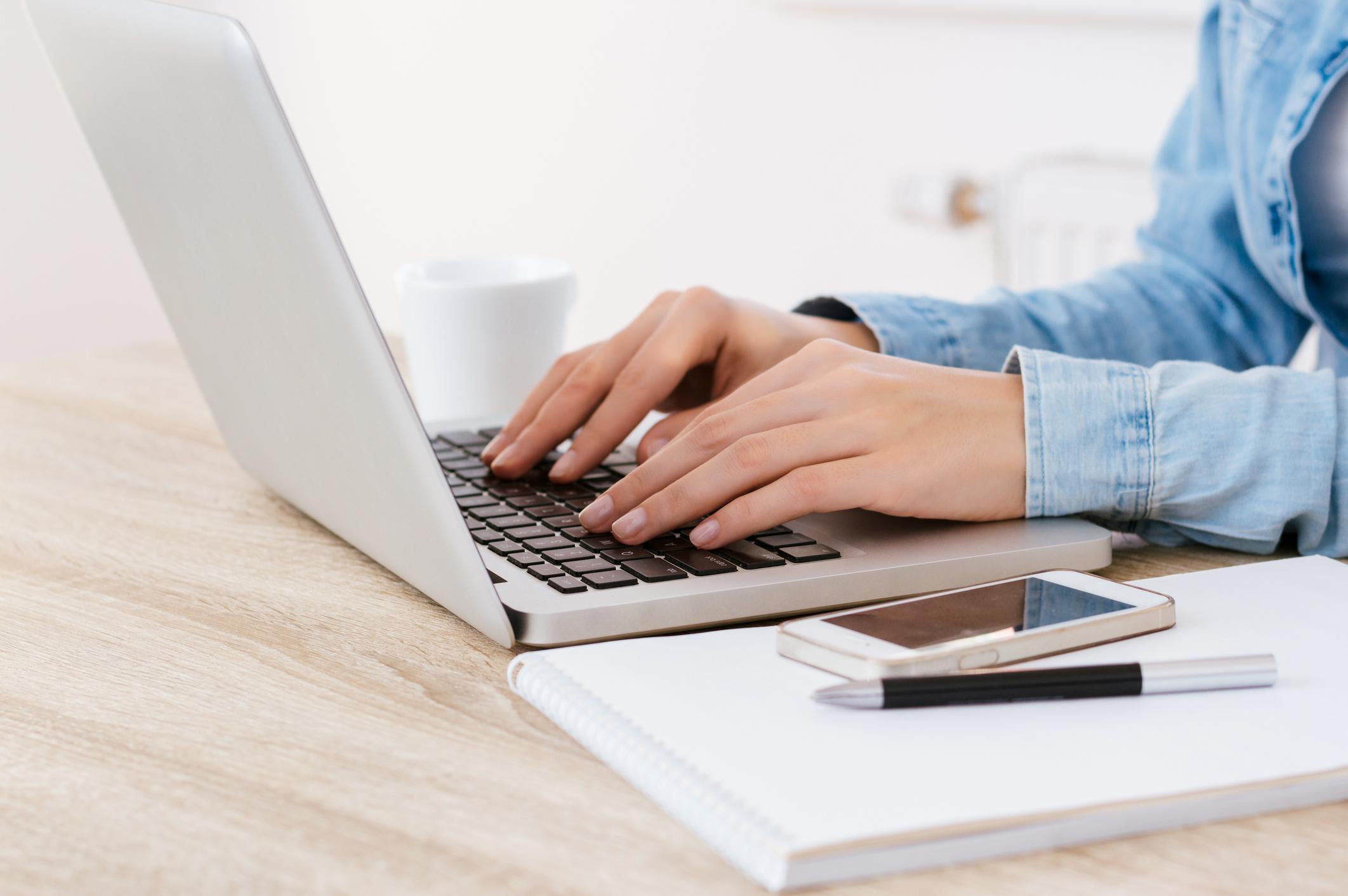 Hands  in denim typing on laptop keyboard